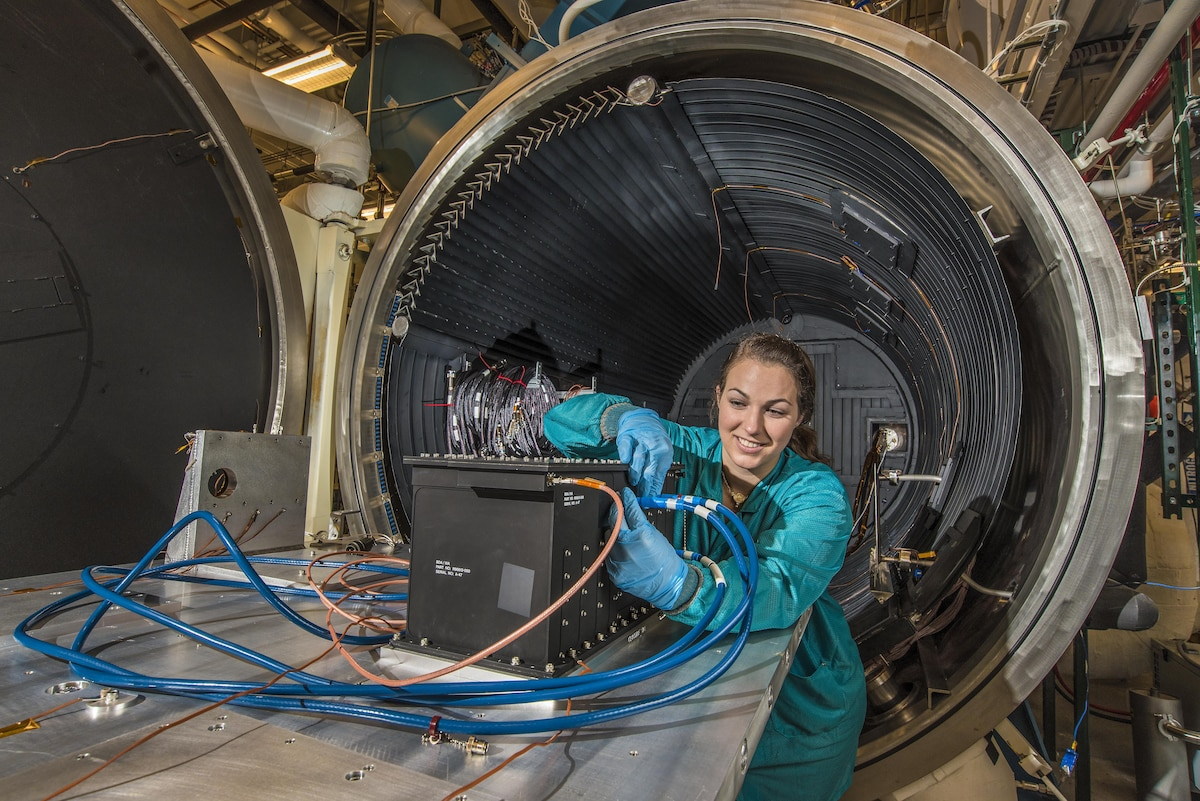 A researcher wearing gloves manipulates wires on a rectangular device in front of a giant metal circular object.