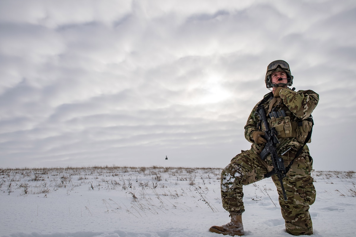 An airman in winter gear stands in a field of snow and looks into the distance.
