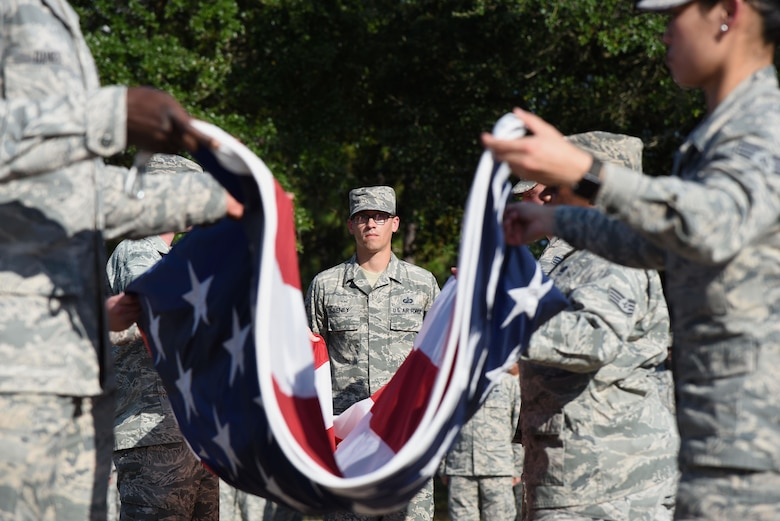 Tech. Sgt. Kevin Seney, 335th Training Squadron instructor, participates in a flag folding ceremony during the POW/MIA Retreat Ceremony Sept. 15, 2017, on Keesler Air Force Base, Mississippi. The event, hosted by the Air Force Sergeants Association Chapter 652, was held to raise awareness and pay tribute to all prisoners of war and military members still missing in action. (U.S. Air Force photo by Kemberly Groue)