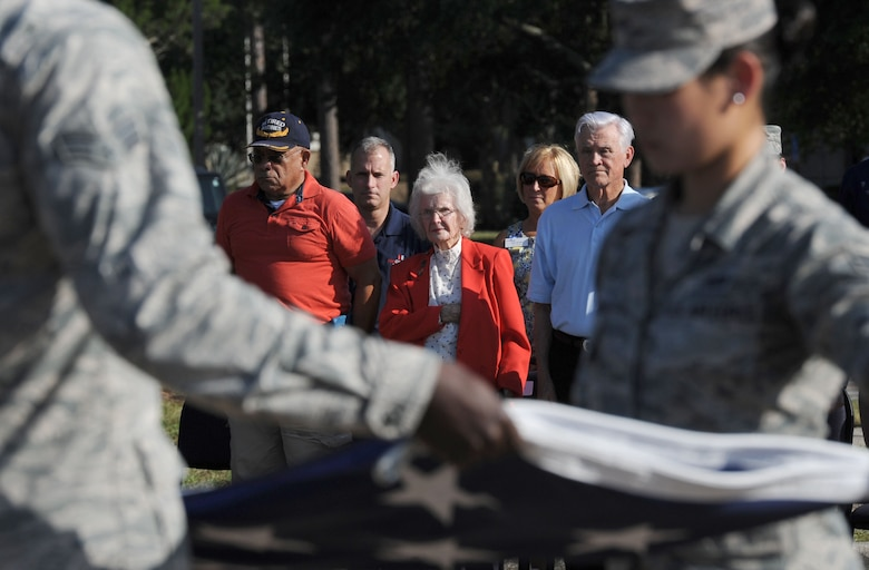 Retired U.S. Marine Corps Capt. Henry Harris, Anna Caire, spouse of Retired Master Sgt. James Caire, former Prisoner of War, and Lt. Col. Barry Bridger, former Prisoner of War, show their respect during the POW/MIA Retreat Ceremony Sept. 15, 2017, on Keesler Air Force Base, Mississippi. The event, hosted by the Air Force Sergeants Association Chapter 652, was held to raise awareness and pay tribute to all prisoners of war and military members still missing in action. (U.S. Air Force photo by Kemberly Groue)
