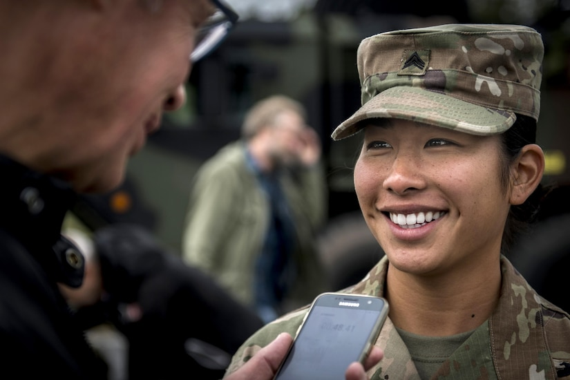 A service member speaks to a person holding a phone.