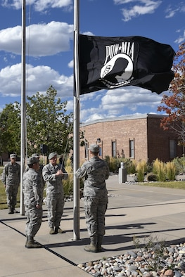 PETERSON AIR FORCE BASE, Colo. – Students from the Forrest L. Vosler Non-Commissioned Officer Academy bring down the American and POW/MIA flags during the Retreat Ceremony, Sept. 17, 2017, at Peterson Air Force Base, Colorado. The Remembrance and Retreat Ceremony concluded the POW/MIA Remembrance week that included a Flag Raising Ceremony and 24-hour run. (U.S. Air Force photo by Craig Denton)