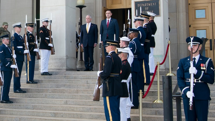 Defense Secretary Jim Mattis stands with Romania's defense minister on steps.