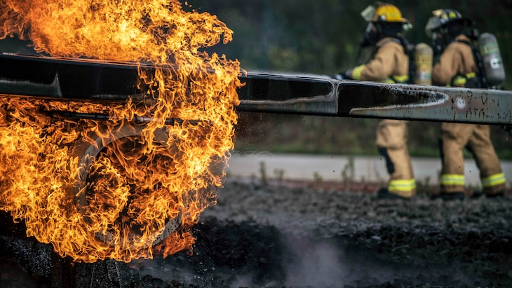 Flames engulf a metal rod as airmen in firefighting garb maneuver in the background.