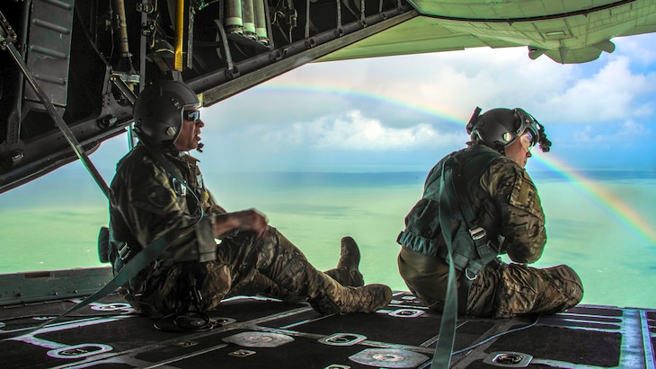 Two service look out  from an aircraft opening over clear water, blue sky and a rainbow.