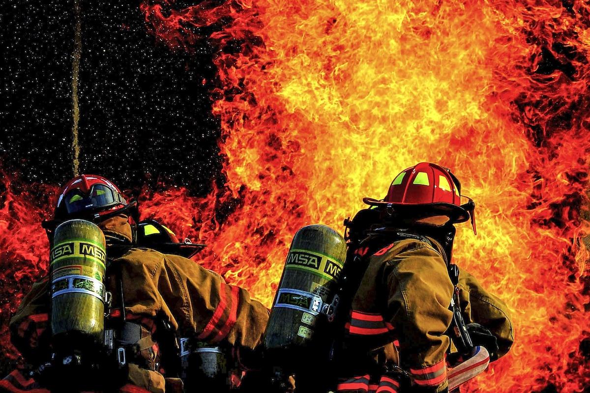 Airmen work to extinguish a large blaze at night.