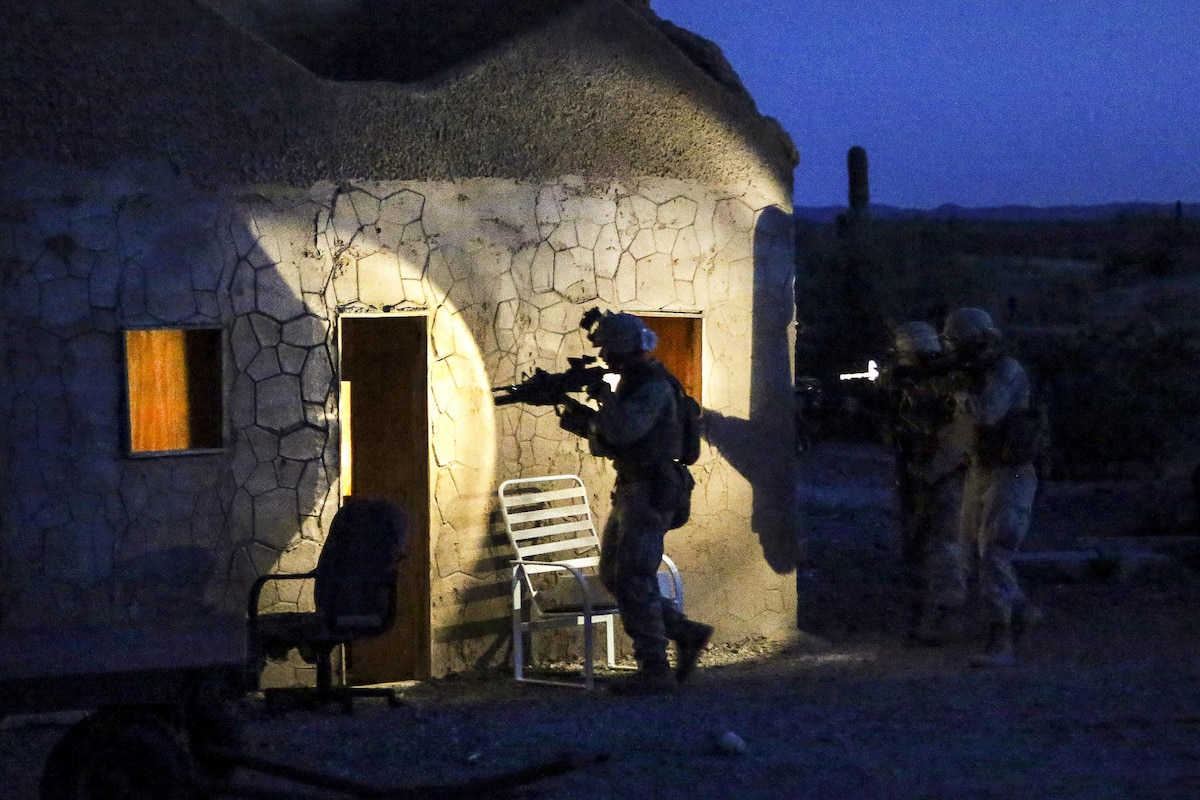 Marines aim their weapons as they approach a building at night.