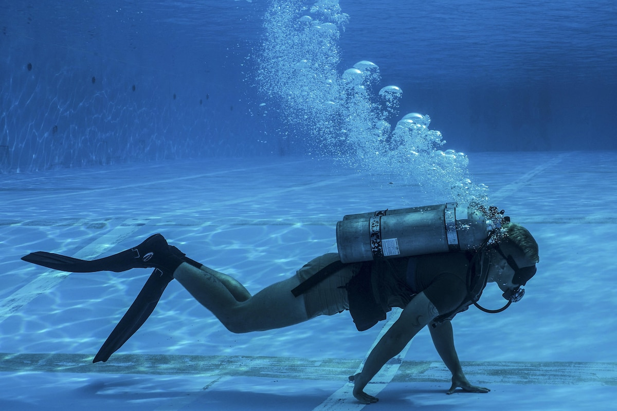 A Marine with breathing gear walks on his hands underwater.
