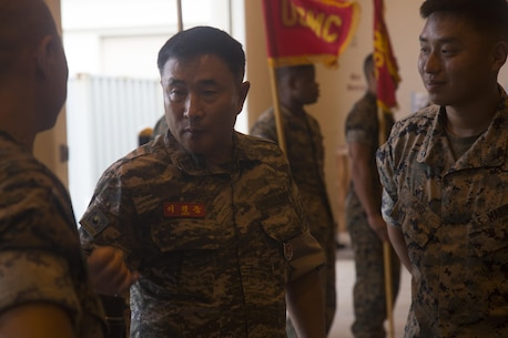 Sgt. Maj. Kyung Woong Lee, left, sergeant major of Republic of Korea Marine Corps, speaks to Marines from Combat Logistics Regiment 35 with his interpreter Lance Cpl. Seong Cho, right, an engine equipment operator with 3d Transportation Support Battalion, during a corporal's course sword and guidon practice Sept. 13, 2017 at Camp Kinser, Okinawa, Japan. Lee is visiting U.S. Marine Corps bases on Okinawa to speak with his U.S. Marine counter parts and observe military education courses.  The 3d Marine Logistics Group is dedicated to building personal and enduring relationships with the ROK MLG by sharing and training with each other in order to become more proficient. (U.S. Marine Corps photo by Lance Cpl. Isabella Ortega)