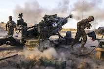 Soldiers fire an artillery weapon, creating clouds of smoke.