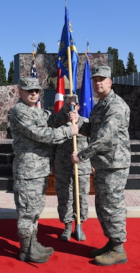 U.S. Air Force Col. David Williams, 39th Mission Support Group commander (left), passes the guidon to Lt. Col. Christopher Collins (right), 425th Air Base Squadron incoming commander, during an Assumption of Command at Izmir Air Station, Turkey, Sept. 18, 2017. Collins was previously assigned to the 451st Flying Training Squadron as a combat systems instructor. (U.S. Air Force photo by Senior Airman Jasmonet D. Jackson)