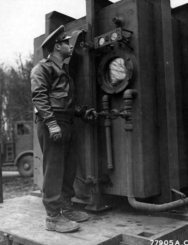 1st Lt. Richard J. Trockman, Evansville, Indiana, at the escape hatch of a low pressure chamber. This chamber is in use by the U.S. Air Force, Headquarters 8th Air Force Provisional Medical Field Service School, High Wycombe, England and is for the purpose of testing the airmen's general physical condition. 24 Feb 1943 (Photo courtesy of the National Archives)