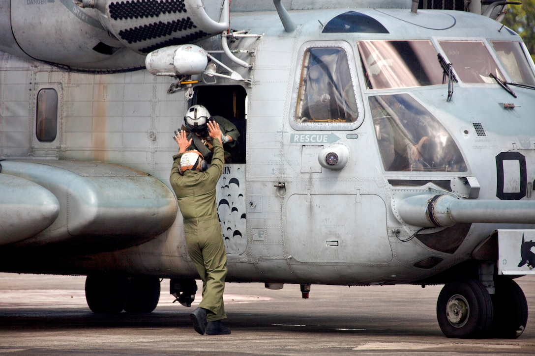 One Marine pilot leaning out a helicopter window high fives another standing outside.