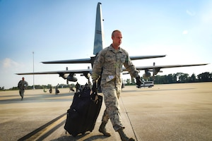 An airman walks with a suitcase behind an aircraft.