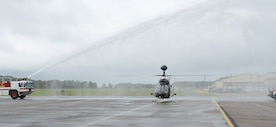 "An OH-58D ""Kiowa Warrior"" passes through water from fire trucks after its final flight at Joint Base Langley-Eustis, Va., Sept. 18, 2017."