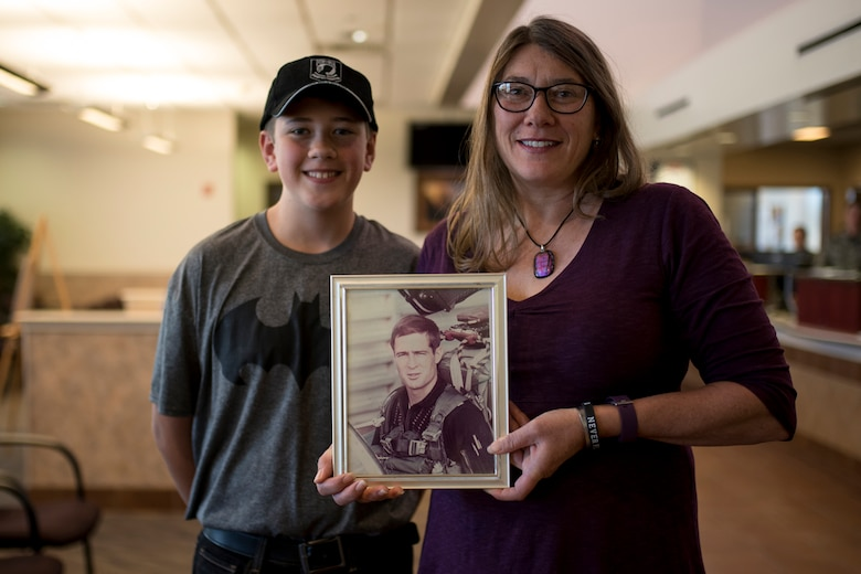 Karin Steadman with her son, Steadman James Brunson, holds a photo of her father at the Visitor Center on Peterson Air Force base, Colorado, Sept. 15, 2017. Karin's Father, Capt. James Steadman, was declared killed in action in 1975. Steadman and her son, who was named for his grandfather, were at Peterson AFB to take advantage of the Gold Star Base Access ID Program that was instituted earlier this year. (U.S. Air Force photo by Senior Airman Dennis Hoffman)