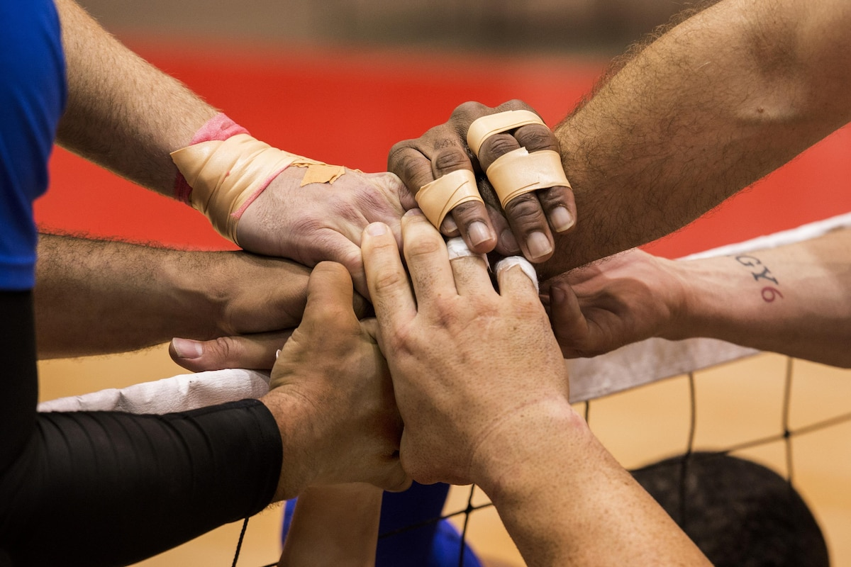 Air Force sitting volleyball team members join hands as a sign of camaraderie