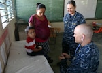 U.S. Navy medical personnel examine a boy at a local medical clinic in Honduras