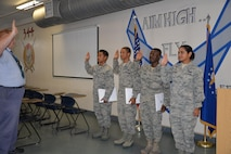 Airmen from the 344 Training Squadron display their immigration packet upon completing the Oath of Allegiance at JBSA-Lackland on Aug. 30.