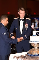 Brig. Gen. Tom Miller, commander of the Oklahoma City Air Logistics Complex, cuts the ceremonial birthday cake along with Airman William Parker from the 72nd Air Base Wing Comptroller Squadron.
