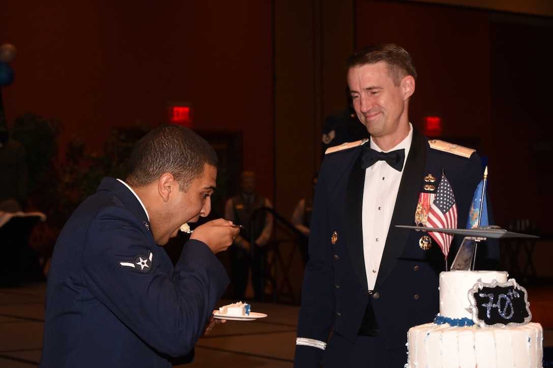 At the Air Force Ball on Sept. 16, 2017, Oklahoma City Air Logistics Center Commander Brig. Gen. Tom Miller, looks on as Airman William Parker from the 72nd Air Base Wing Comptroller Squadron, takes the first bite of the ceremonial cake to honor the U.S. Air Force's 70th birthday.