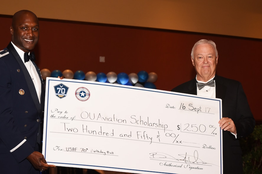 Col. Kenyon Bell, 72nd Air Base Wing commander, presents Garry Richey, former Oklahoma City Air Logistics Center executive director, with a $250 check for the OU Aviation Scholarship as a 'thank you' for being the guest speaker of this year's Air Force Ball on Sept. 16.