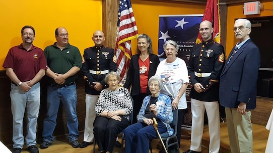 Staff Sgts. Michael Tomlin and Jonathan Wright stand with former and retired Marine veterans as well as members of the Women Marine Association after presenting Martha Potter (seated left) and Mary Paquette, World War II veterans, with Victory Medals at the Southside Tavern in Manchester, N.H., Sept. 16, 2017. Many of the small contingent of the Women Marine Reserves during WWII were discharged from the service following the conclusion of the war, and as such were not awarded the Victory Medal. The Area 1 chapter of the WMA teamed with Marines of Recruiting Station Portsmouth, N.H., to identify and present such women with the medals. Tomlin is a canvassing recruiter with Recruiting Substation Dover, N.H., and Wright is the Marketing and Communications Chief for RS Portsmouth.