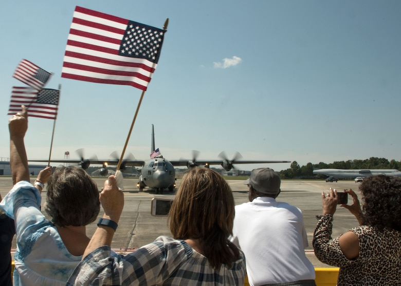 Family members wave American flags as a group of C-130H3 Hercules taxied into place on the flightline at Dobbins Air Reserve Base, Ga. Sept. 18, 2017. The aircrews were returning to Dobbins after a four-month deployment to the Middle East in support of contingency operations. (U.S. Air Force photo/Staff Sgt. Andrew Park)