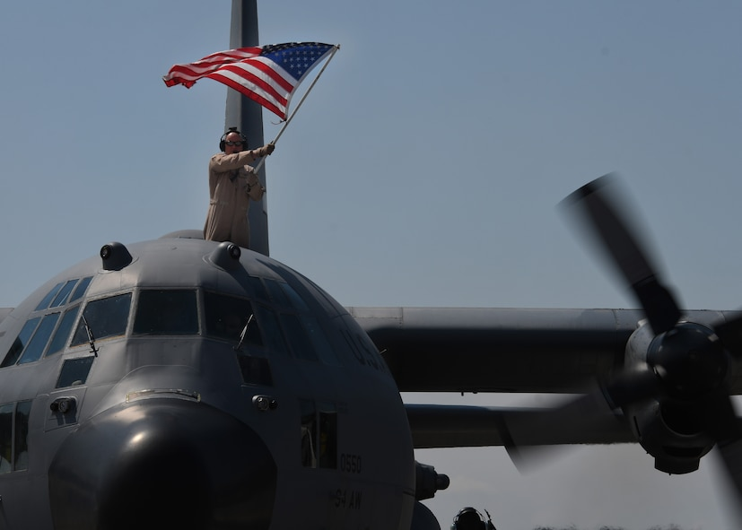 A service member holds an American Flag from the top of a C-130H3 Hercules at Dobbins Air Reserve Base, Ga, Sept. 18, 2017. Five aircraft, along with their aircrews, returned to the 94th Airlift Wing following a deployment to Al Udeid Air Base, Qatar. (U.S. Air Force Photo by Staff Sgt. Miles Wilson)