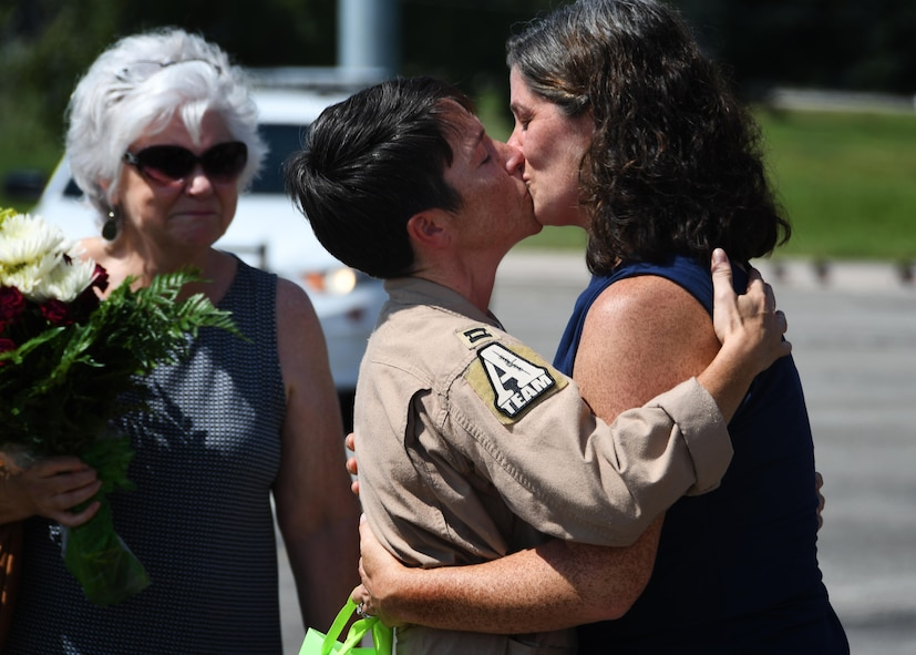 Capt. Rendi Clegg, 700th Airlift Squadron navigator, kisses her wife at Dobbins Air Reserve Base, September 18, 2017. Glegg returned to Dobbins after a four month deployment to Al Udeid Air Base, and found wife waiting for her, along with the friends and family of the other Deployers who arrived with Clegg. (U.S. Air Force Photo by Staff Sergeant Miles Wilson)