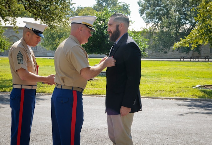 SAN ANTONIO (Sept. 8, 2017)  Lt. Col. William O'Brien, commanding officer, 3D Assault Amphibian Battalion in Camp Pendleton, California, pins the Navy and Marine Corps Medal on Marine Corps veteran Corporal Randy D. Mann during a ceremony in the historical quadrangle at Joint Base San Antonio - Fort Sam Houston, Texas. Mann was awarded the medal during the ceremony in his hometown of San Antonio for his heroic actions while on active duty with the 3D Assault Amphibian Battalion in July 2013. (U.S. Navy photo by Mass Communication Specialist 1st Class Jacquelyn D. Childs/Released)