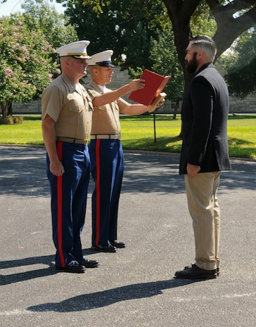 SAN ANTONIO (Sept. 8, 2017) Command Sgt. Maj. Max Garcia, center, 3D Assault Amphibian Battalion in Camp Pendleton, California, reads an award citation for Marine Corps veteran Corporal Randy D. Mann, right, while Lt. Col. William O'Brien, commanding officer stands at attention during a ceremony in the historical quadrangle at Joint Base San Antonio - Fort Sam Houston, Texas. Mann was awarded the Navy and Marine Corps Medal during the ceremony in his hometown of San Antonio for his actions while on active duty with the 3D Assault Amphibian Battalion in July 2013. (U.S. Navy photo by Mass Communication Specialist 1st Class Jacquelyn D. Childs/Released)