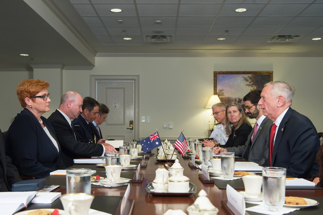 Defense Secretary Jim Mattis sits at a table with several other people.