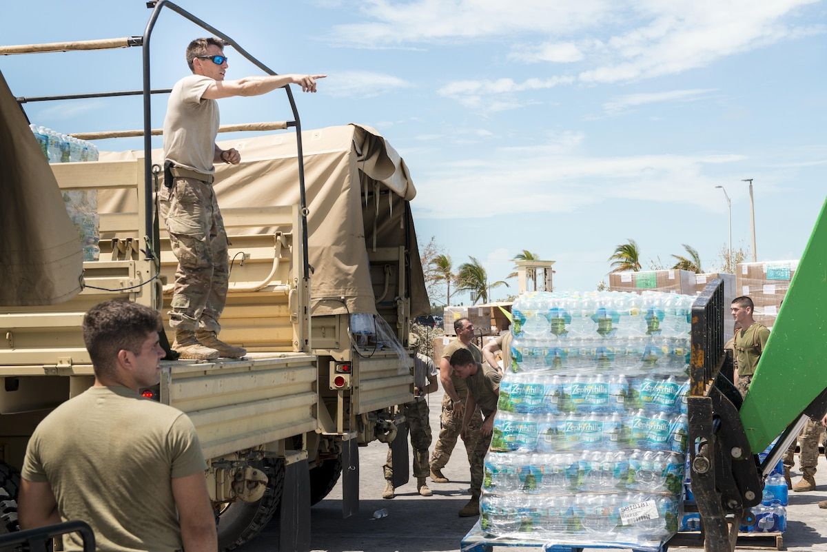 Guardsmen move pallets of water.