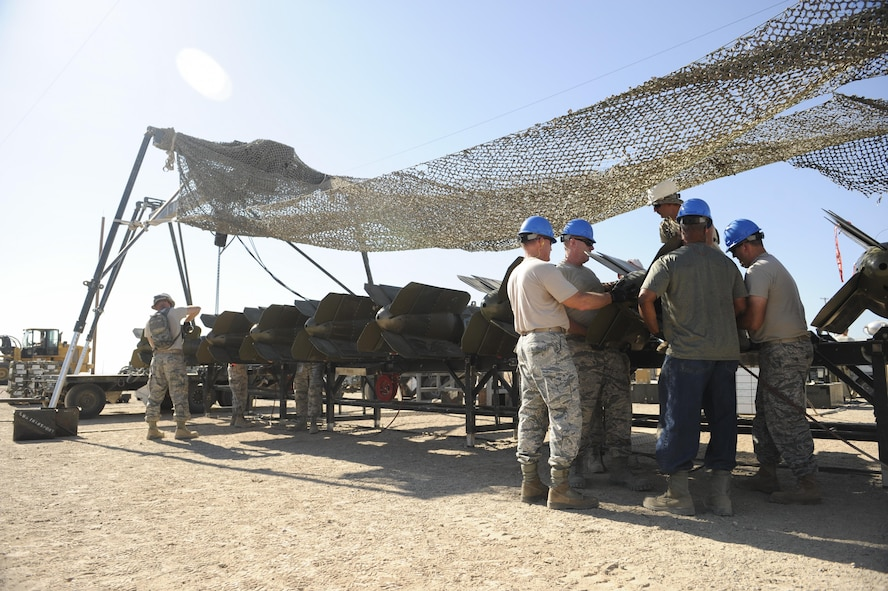 Senior officers (blue helmets) work in conjunction with munitions Airmen during an officer orientation course geared toward giving them a hands on experience on the tactical demands of bomb building at Beale Air Force Base, California, August 30, 2017. The munitions were assembled on a mobile Munitions Assembly Conveyor. (U.S. Air Force photo/Senior Airman Justin Parsons)