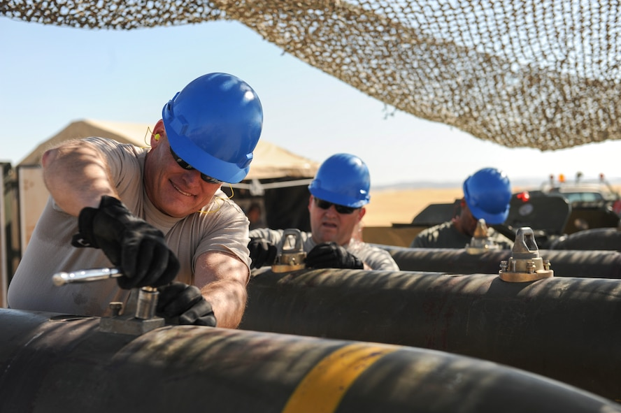 Senior officers and contractors make a final inspection of all fasteners on the bodies of a MK-84 bomb to ensure it meets set standards at Beale Air Force Base, California, Aug. 30, 2017. The weapon system is required to meet all assembly standards to ensure the munitions functions correctly when deployed. (U.S. Air Force photo/Senior Airman Justin Parsons)