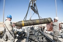 Maj. Allyn Swavely, a participant in the Senior Officer Orientation course, helps guide the body of a MK-84 onto the Munitions Assembly Conveyor at Beale Air Force Base, California, Aug. 30, 2017. Bombs built by munitions Airmen can range in weight up to approximately 2,000 lbs and have multiple configurations depending on operational demands. (U.S. Air Force photo/Senior Airman Justin Parsons)