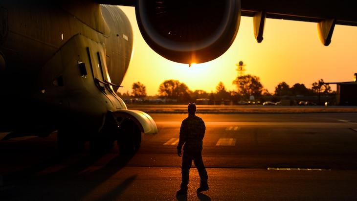 An airman walks around an aircraft at sunset.