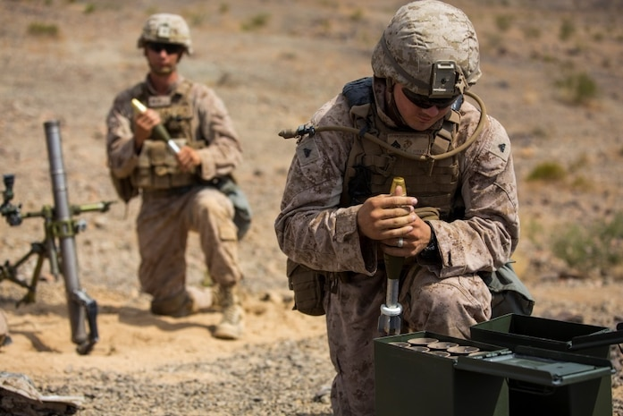 Cpl. Christopher Stephens, mortarman, 1st Battalion, 1st Marine Regiment, prepares rounds for Pfc. Thomas Curtis, mortarman, 1/1, during an individual training exercise at Range 410A aboard the Marine Corps Air Ground Combat Center, Twentynine Palms, Calif., July 25, 2017. 1/1 is based out of Marine Corps Base Camp Pendleton, Calif. and is serving as part of the GCE during ITX 5-17.  (U.S. Marine Corps photo by Pfc. Margaret Gale)