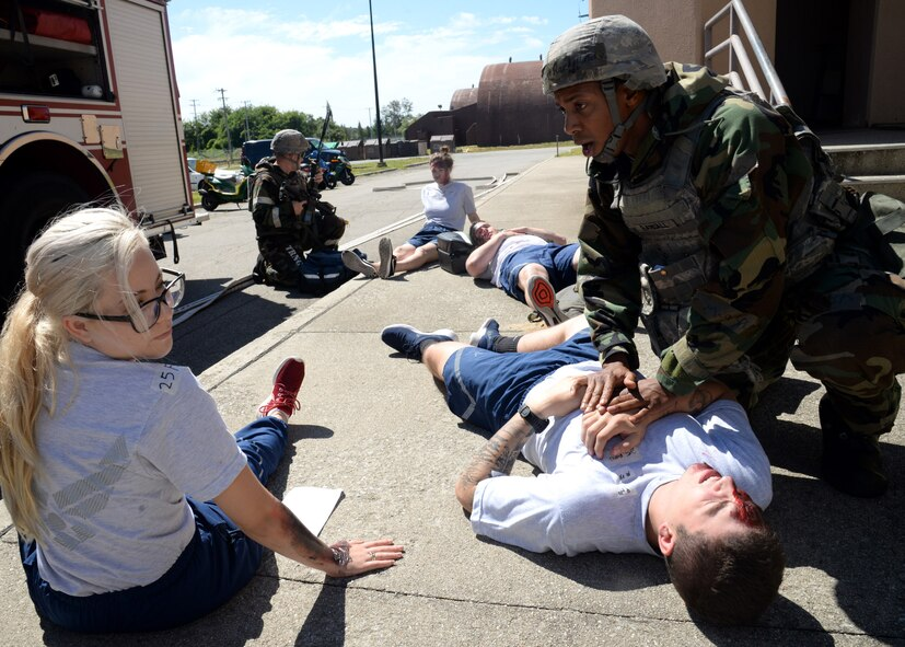 Tech Sgt. Michael Randall, far right, 51st Security Forces Squadron defender, attends to the wounds of multiple victims during a simulated building fire portion of exercise Beverly Herd 17-3 at Osan Air Base, Republic of Korea September 20, 2017. The exercise was held to evaluate the readiness and initial actions of the base First Response Team under realistic scenario simulations. (U.S. Air Force photo by Tech Sgt. Ashley Tyler)