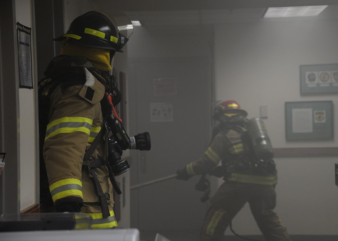 Senior Airman Kristopher Morgan, left, 51st Civil Engineer fire department driver operator, secures the area while Staff Sgt. Sean Douglas, 51st Civil Engineer fire department crew chief, pulls in the fire hose to extinguish a simulated building fire during exercise Beverly Herd 17-3 at Osan Air Base, Republic of Korea September 20, 2017. The exercise was held to evaluate the readiness and initial actions of the base First Response Team under realistic scenario simulations. (U.S. Air Force photo by Tech Sgt. Ashley Tyler)