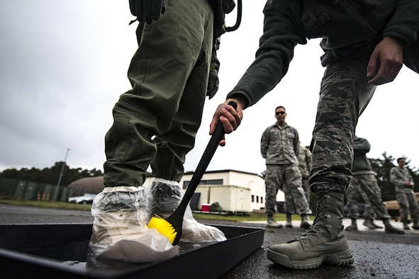 A U.S. Air Force Aircrew Flight Equipment technician decontaminates another AFE technician in a boot wash tray during the Aircrew Contamination Mitigation course on Ramstein Air Base, Germany, Sept. 19, 2017.