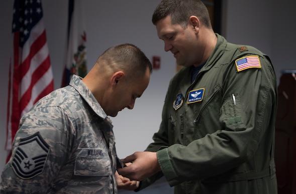Maj. Ben Simerman pins the Military Outstanding Volunteer Service Medal on Senior Master Sgt. Kevan Williams.