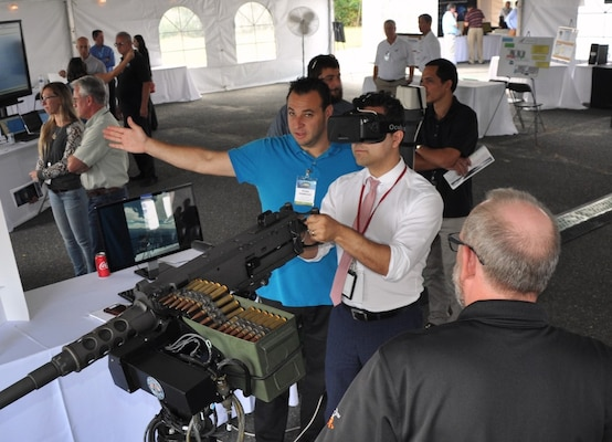 IMAGE: DAHLGREN, Va. (Sept. 14, 2017) - A visitor wearing augmented reality glasses at the 2017 Annual Navy Technology Exercise (ANTX) engages in mixed reality training  as he fires on fast attack craft and fast inshore attack craft (FAC-FIAC) with an M-2HB .50 caliber machine gun simulator. The FAC/FIAC Integrated Training Portable Embarkable Kit was one of many Navy Innovative Science and Engineering (NISE) funded projects on display at ANTX. The NISE FAC/FIAC project extends Fleet  Synthetic Training to a pier-side ship for an all-inclusive self-defense training scenario against a surface swarm attack.