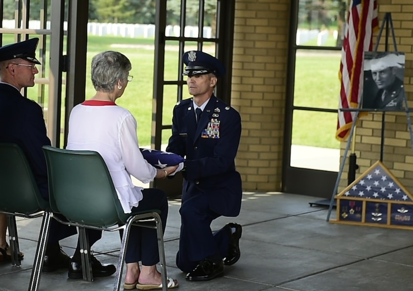 Lt. Col. Thomas J. Nefe, Director of Resources and Readiness, 240th Civil Engineer Flight, Colorado Air National Guard, Buckley AFB, presents the American flag to Linne (Royal) Haddock during the memorial service at Logan National Cemetery in Denver for Haddock's father, Col. Frank Royal, who passed away in November. Royal commanded the 39th Fighter Squadron during World War II in New Guinea, making one air-to-air kill July 4, 1942. (Photo by Senior Airman Alyssa Duprey, 460th Space Wing Public Affairs).
