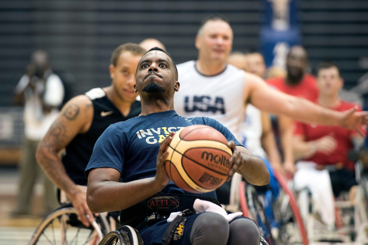 An athlete in a wheelchair holds up a basketball before throwing it.