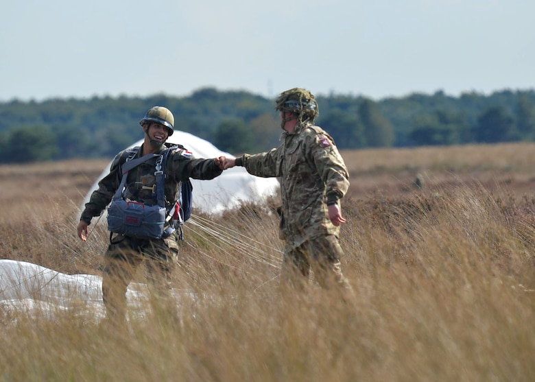 French and British paratroopers congratulate each other after successfully landing on the drop zone during exercise Falcon Leap Sept. 15, 2017, at the Houtdorperveld Drop Zone, Netherlands. Approximately 750 paratroopers from eight different countries participated in exercise Falcon Leap and the commemoration of Operation Market Garden. (U.S. Air Force photo by Airman 1st Class Codie Collins)