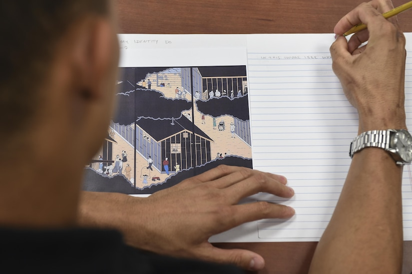Members of Joint Base Charleston wrote their interpretation on a drawing of a World War II Japanese-American internment camp for a Multicultural Diversity: Real Talk workshop at the Air Base Education Center here Sept. 19, 2017.