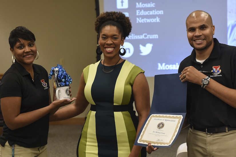 Staff Sgt. Marica Moore, 628th Air Base Wing Equal Opportunity advisor, left, and Toby Housey, 628th ABW EO director, right, present an award to Dr. Melissa Crum, Mosaic Education Network founder and diversity practitioner, for her contribution to the Multicultural Diversity: Real Talk workshop at the Air Base Education Center here Sept. 19, 2017.