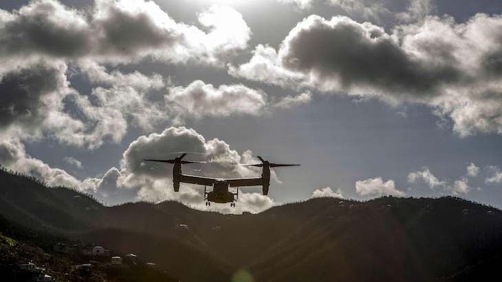A tiltrotor aircraft flies in a mountainous area.